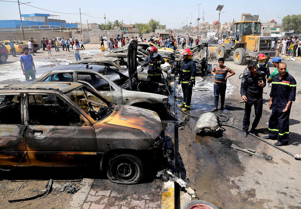 . Iraqi firefighters extinguish vehicles after a car bomb explosion in the Shiite stronghold of Sadr City, in Baghdad, Iraq, Tuesday, May 13, 2014.  (AP Photo/Karim Kadim)