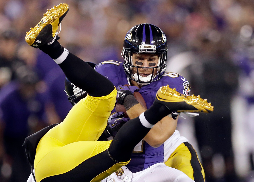 . Baltimore Ravens tight end Owen Daniels (81) hangs on to the ball as he is tackled by Pittsburgh Steelers free safety Mike Mitchell, who is upside down, during the second half of an NFL football game Thursday, Sept. 11, 2014, in Baltimore. (AP Photo/Patrick Semansky)