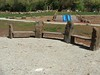rock and timber seating and dual blue plastic slide on embankment with timber hand rails and clambering