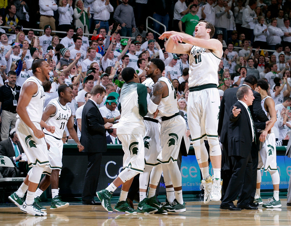 . Michigan State players, including Matt Costello (10) celebrate during the second half of an NCAA college basketball game against Michigan, Sunday, Feb. 1, 2015, in East Lansing, Mich. Michigan State won 76-66 in overtime. (AP Photo/Al Goldis)