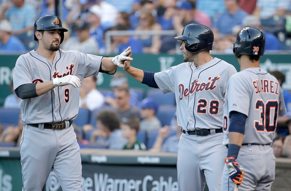 . Detroit Tigers\' Nick Castellanos (9) and J.D. Martinez (28) celebrate after Martinez scored on a sacrifice fly hit by Castellanos during the first inning of a baseball game against the Kansas City Royals Thursday, July 10, 2014, in Kansas City, Mo. (AP Photo/Charlie Riedel)