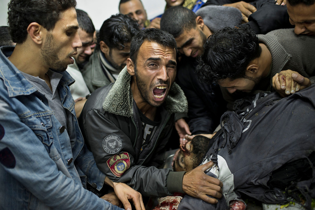 . In this Nov. 18, 2012 file photo, a Palestinian man cries next the body of a dead relative in the morgue of Shifa Hospital in Gaza City. This photo was one in a series of images by Associated Press photographer Bernat Armangue that won the first place prize in the World Press Photo 2013 photo contest for the Spot News series category.  (AP Photo/Bernat Armangue, File)