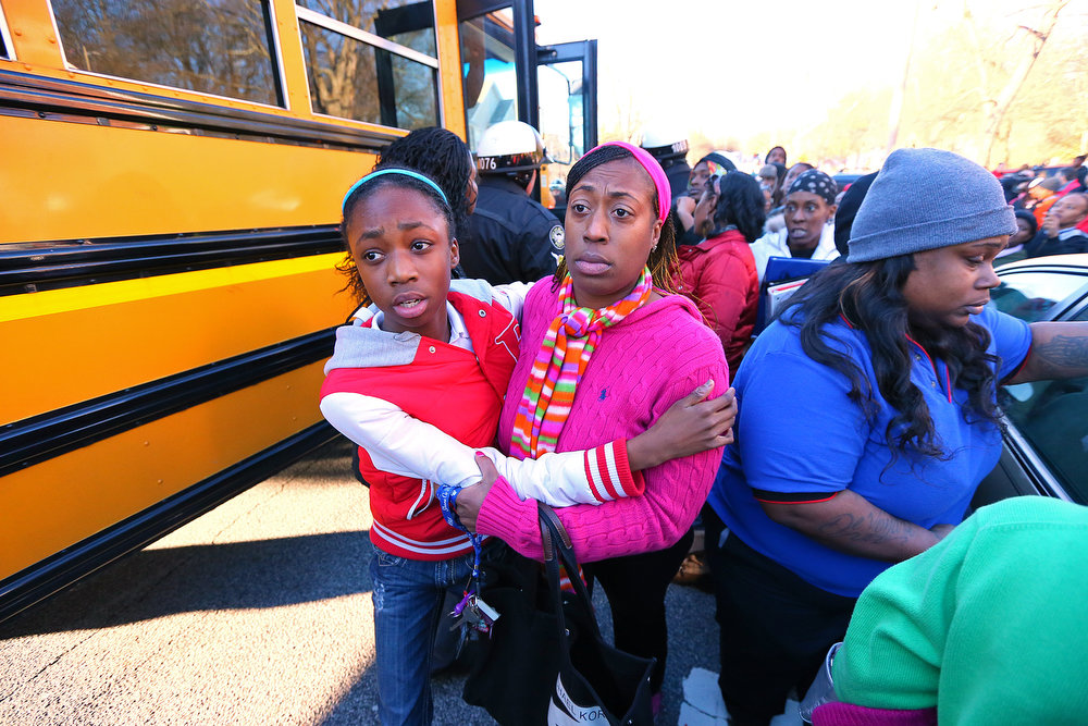 . Mother and daughter embrace as Tiffany Myricle, 37, leads her daughter Xavia Denise Myricle away from her school bus when parents and children are reunited at Emmanuel Baptist Church after a shooting at an Price Middle school in Atlanta on Thursday, Jan. 31, 2013. A 14-year-old boy was wounded outside the school Thursday afternoon and a fellow student was in custody as a suspect, authorities said. No other students were hurt. (AP Photo/Atlanta Journal-Constitution, Curtis Compton)