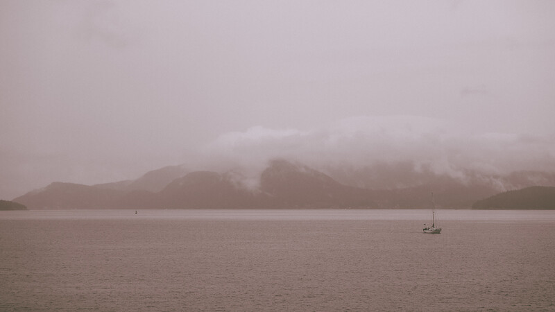 A boat without its sail up glides through the ocean waters during a cloudy, foggy morning.