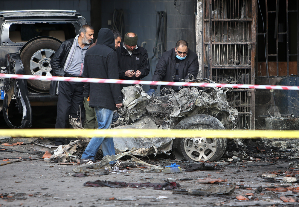 . Lebanese police inspectors investigate the site of a deadly car bomb that exploded Saturday evening near a gas station in the predominately Shiite town of Hermel, about 10 miles (16 kilometers) from the Syrian border, in northeast Lebanon, Sunday, Feb. 2, 2014. (AP Photo/Hussein Malla)
