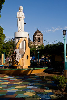 A workman paints a statue in a park in front of the Iglesia San Juan de Dios