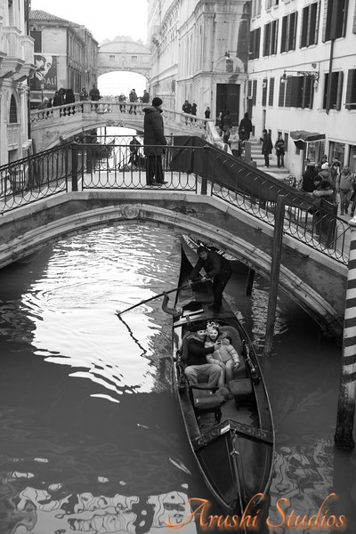 A closer view of another gondola going under a bridge conneting two islands of venice.