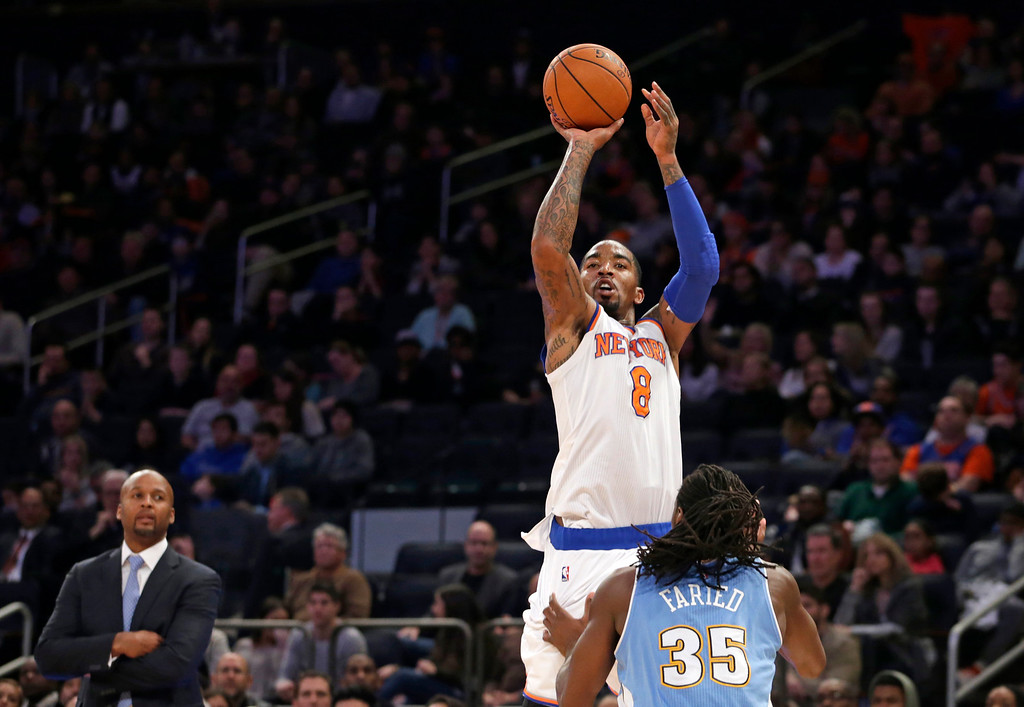 . Denver Nuggets head coach Brian Shaw watches, far left, as New York Knicks guard J.R. Smith (8) shoots over the defense of Denver Nuggets forward Kenneth Faried (35) in the second half of an NBA basketball game at Madison Square Garden in New York, Sunday, Nov. 16, 2014. Smith and Carmelo Anthony each had 28 points to help the Knicks defeat the Nuggets 109-93. (AP Photo/Kathy Willens)
