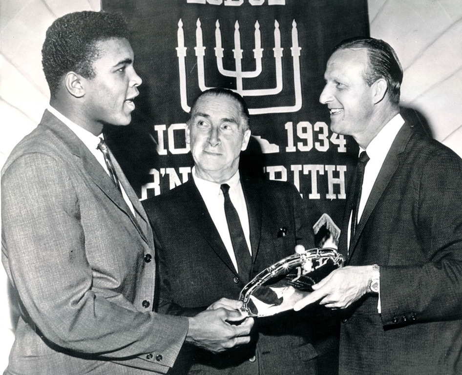 . Cassius Clay, heavyweight boxing challenger, (left) and Stan Musial of the St. Louis Cardinals, (right) receive awards at the annual B\'nai B\'rith sports dinner in Boston tonight.  Making the awards is Horace McMohn, star of the television show, \'Naked City.\' 1962. Credit: AP