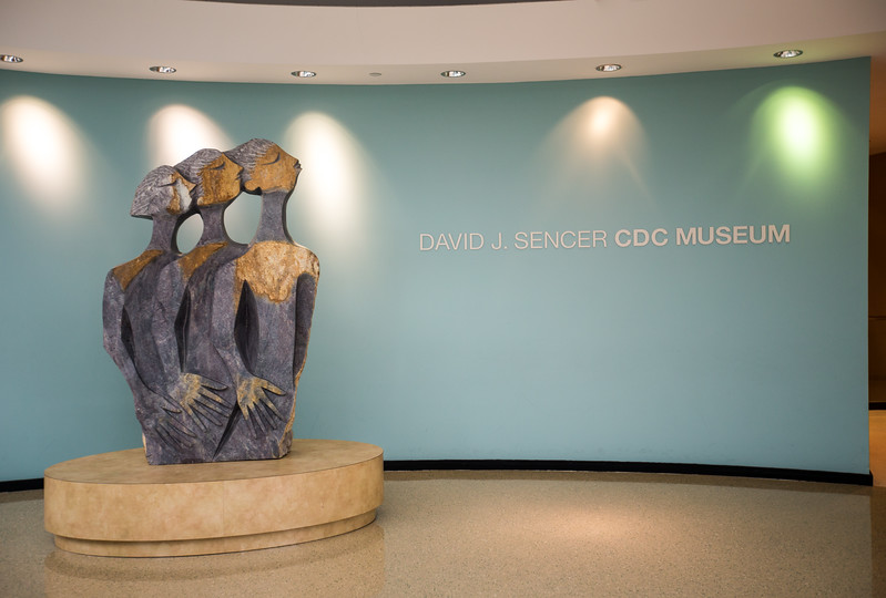 """Behind the high-level security at the CDC is the David J. Sencer CDC Museum where """"The Messengers,"""" a serpentine stone scuplture created by Lameck Bonjisi greats guests to the museum.  The piece reflects the Zimbabwean culture and serves to represent the CDC mission to educate all who visit about the interconnection of public health, culture and community.  The museum highlights information and history of AIDS, Smallpox, Legionnaires' Disease, Venereal Disease, Ebola and much more.  (Jenni Girtman / Atlanta Event Photography)"""