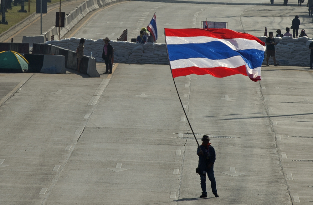 """. An anti-government protester waves a national flag as they block intersection during rally in Bangkok on January 13, 2014.  Thai opposition protesters launched their attempted \""""shutdown\"""" of Bangkok, occupying key intersections in the capital in an escalation of their campaign to unseat Prime Minister Yingluck Shinawatra. (PORNCHAI KITTIWONGSAKUL/AFP/Getty Images)"""