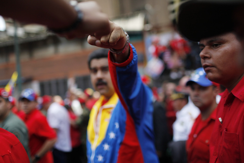 . Venezuela\'s Vice President Nicolas Maduro, center, bumps fists with a supporter as he walks alongside the coffin of Venezuela\'s late President Hugo Chavez as it is taken from the hospital where Chavez died on Tuesday to a military academy in Caracas, Venezuela, Wednesday, March 6, 2013. Maduro will continue to run Venezuela as interim president and be the governing socialists\' candidate in an election to be called within 30 days. (AP Photo/Rodrigo Abd)