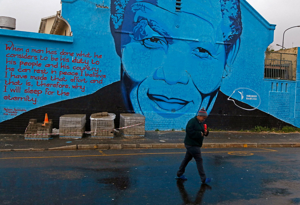 . A woman walks past a mural with the face of former South African President Nelson Mandela in Cape Town, South Africa, Friday, July 18, 2014. South Africans marked the late Nelson Mandela\'s birthday on Friday with charitable acts in honor of the former president, whose death in December prompted a global outpouring of tributes. Organizers had urged people to perform acts of charity for 67 minutes, symbolizing the anti-apartheid leader\'s 67 years of public service. (AP Photo/Schalk van Zuydam)