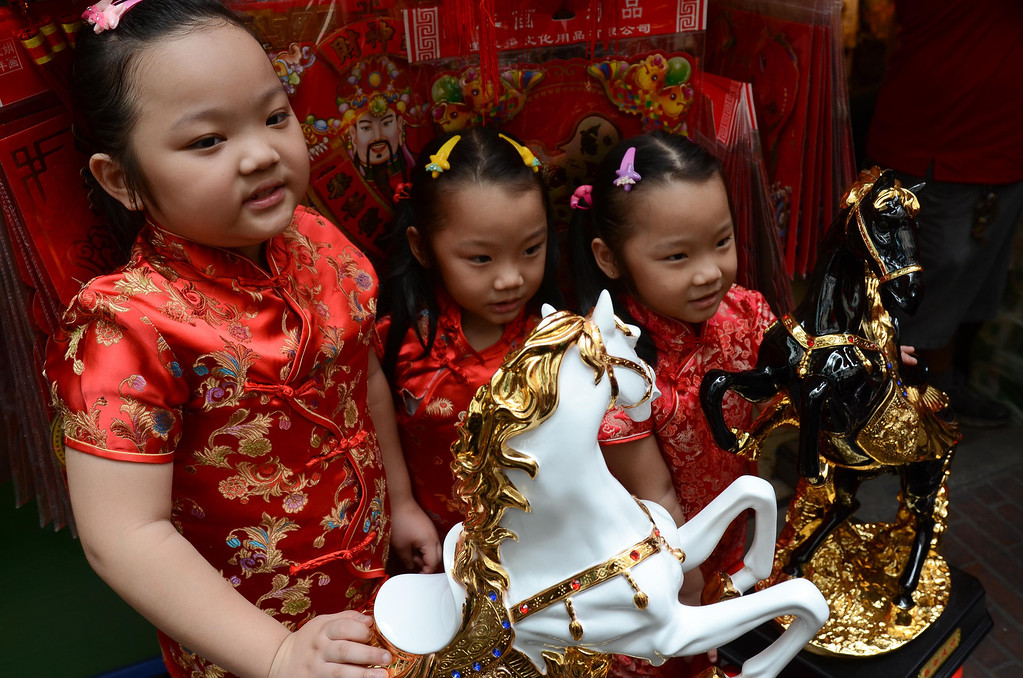 . Children dressed in the traditional Chinese Cheongsam pose before a horse figurine in the Chinese district of Binondo on January 31, 2014 in Manila, Philippines.   (Photo by Dondi Tawatao/Getty Images)