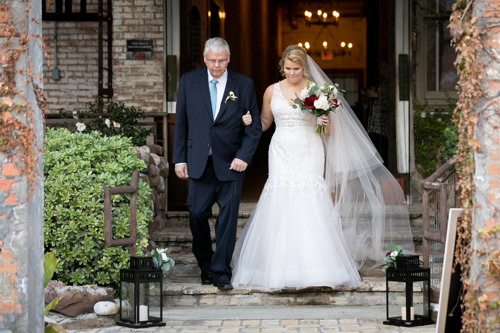bride being walked down steps to the aisle by her father