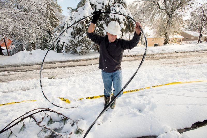 . Scott Springer, an engineer with the North Little Rock Electric Department moves a fallen power line away from the street on Lakeview Road in North Little Rock on Wednesday, Dec. 26, 2012. Spotters were out assessing where downed lines were so crews could make line repairs easier.  Much of North Little Rock saw more than nine inches of snow on Christmas day. (AP Photo/Arkansas Democrat-Gazette, Karen E. Segrave)