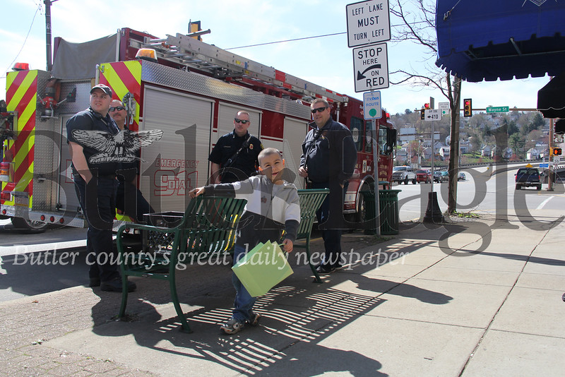Kevin and Chelaina O'Brien's six-year-old son stands in front of a Butler City fire truck Saturday on Main Street.