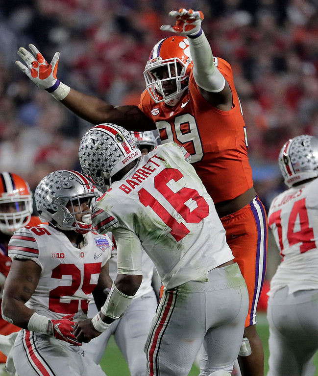 . Clemson defensive end Clelin Ferrell (99) pressures Ohio State quarterback J.T. Barrett (16) after the throw during the second half of the Fiesta Bowl NCAA college football game, Saturday, Dec. 31, 2016, in Glendale, Ariz. (AP Photo/Rick Scuteri)