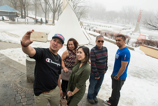 DAVID LIPNOWSKI / WINNIPEG FREE PRESS   Taking off their jackets for a photo, (left to right) Jaime Romero takes a selfie with Tonet Yangyang, Ana Romero, Felizardo Yangyang, Jay Batan from Regina at The Forks during abnormally warm weather Sunday January 22, 2017.