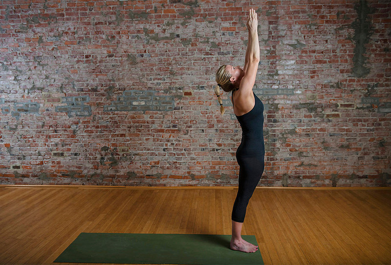 . Yoga instructor Mimi Rieger demonstrates a sun salutation sequence.  2) Lift your arms over your head while inhaling, creating length in your spine and limbs.  (Photo for The Washington Post by Amanda Voisard.)