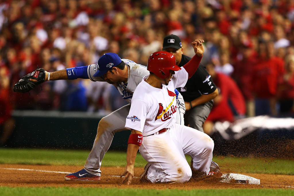 . ST LOUIS, MO - OCTOBER 11:  Jon Jay #19 of the St. Louis Cardinals is out at first by Adrian Gonzalez #23 of the Los Angeles Dodgers on a double play on a ball hit by David Freese #23 in the seventh inning during Game One of the National League Championship Series at Busch Stadium on October 11, 2013 in St Louis, Missouri.  (Photo by Elsa/Getty Images)