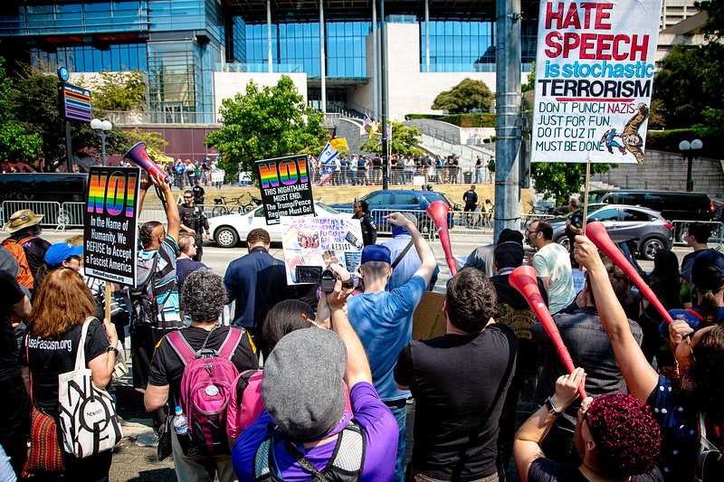 Anti-fascist protestors hold up signs and blow on vuvuzelas at the right-wing rally being held at Seattle City Hall.