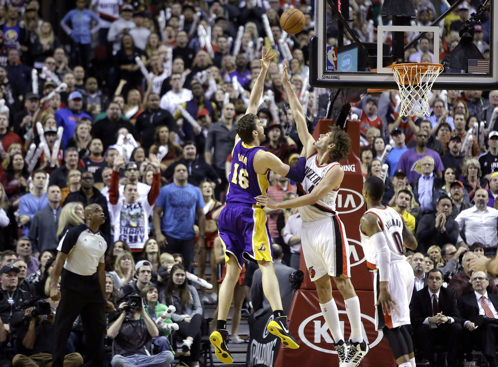 . Los Angeles Lakers center Pau Gasol, from Spain, left, shoots over Portland Trail Blazers center Robin Lopez during the second half of an NBA basketball game in Portland, Ore., Monday, March 3, 2014. Gasol topped the Lakers in scoring with 22 points as they won 107-106. (AP Photo/Don Ryan)