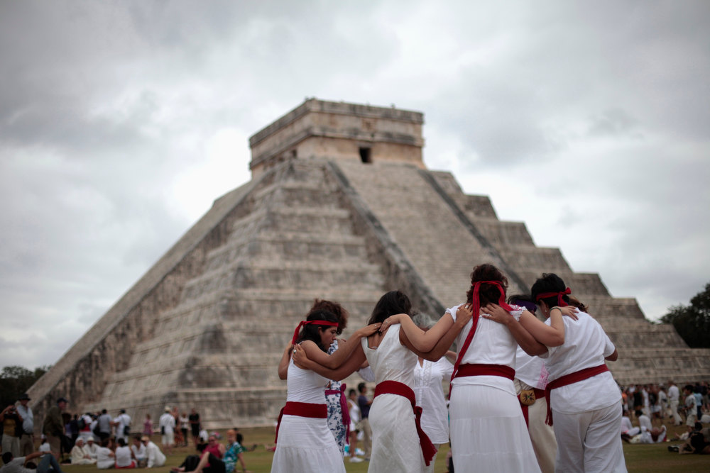 . People perform a ritual in front of the pyramid of Kukulkan at the archaeological site of Chichen Itza in Yucatan State, Mexico, December 21, 2012. Thousands of mystics, hippies and tourists celebrated in the sunshine of southeastern Mexico on Friday as the Earth survived a day billed by doomsday theorists as the end of the world and a new era began for the Maya people. New Age dreamers, alternative lifestyle gurus and curious onlookers from around the world descended on the ruins of Maya cities to mark the close of the 13th bak\'tun - a period of around 400 years - and many hoped it would lead to a better era for humanity. REUTERS/Victor Ruiz Garcia