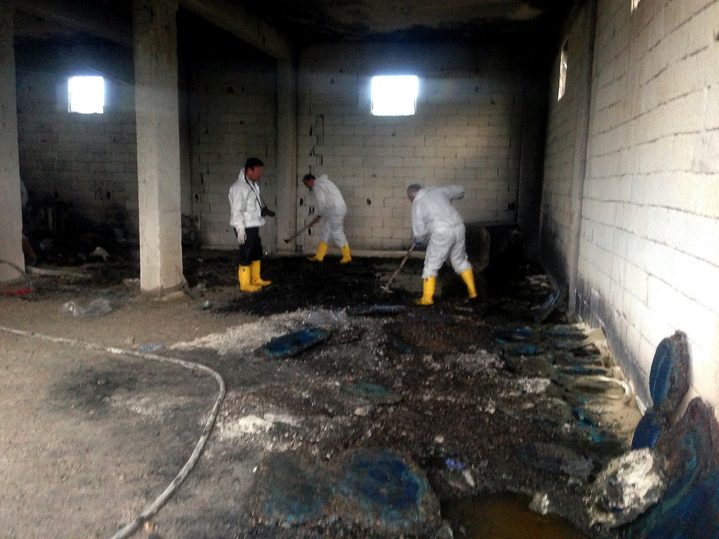 . Forensic police officers work inside an illegal fuel depot on May 17, 2013, after suspects set ablaze the depot located in the basement of a three-storey building in a small village near Turkey\'s border with Syria, triggering a strong explosion that killed at least ten people and wounded nine others. Among the wounded were three suspected smugglers as well as several security officers, Anatolia news agency reported. STR/AFP/Getty Images