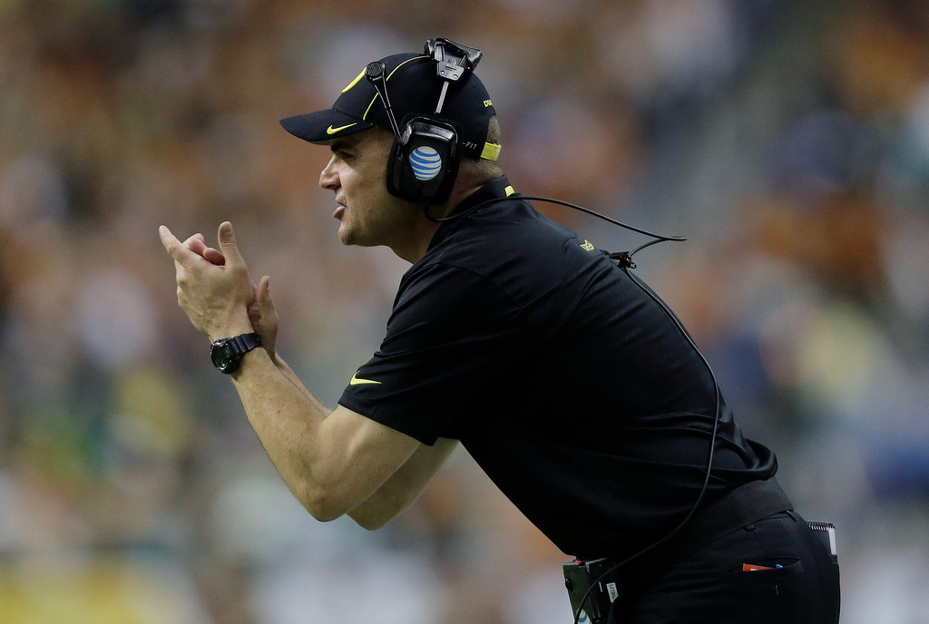. Oregon coach Mark Helfrich talks to his players during the first half of the Valero Alamo Bowl NCAA college football game against Texas, Monday,  Dec. 30, 2013, in San Antonio. Oregon won 30-7.  (AP Photo/Eric Gay)
