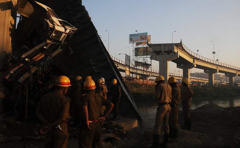 . Indian onlookers and firefighters stand near the collapsed portion of a flyover in Kolkata on March 3, 2013. A huge portion of a flyover on the eastern side of the Indian metropolis collapsed leaving three persons injured, the flyover connects the airport with Eastern Metropolitan Bypass and the eastern and southern suburbs.   As the debris fell into a canal running below the flyover, it took down a truck the driver and two others were rescued from the canal by fire-brigade personnel and locals.   DIBYANGSHU SARKAR/AFP/Getty Images