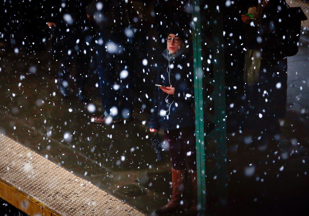 . A commuter, with ear plugs tethered to a phone, is sheltered from snowfall while waiting on a subway platform, Tuesday March 13, 2018, in the Brooklyn borough of New York. The National Weather Service predicted between two and five inches of snow in the city and surrounding areas, where a winter weather advisory was in effect. (AP Photo/Bebeto Matthews)