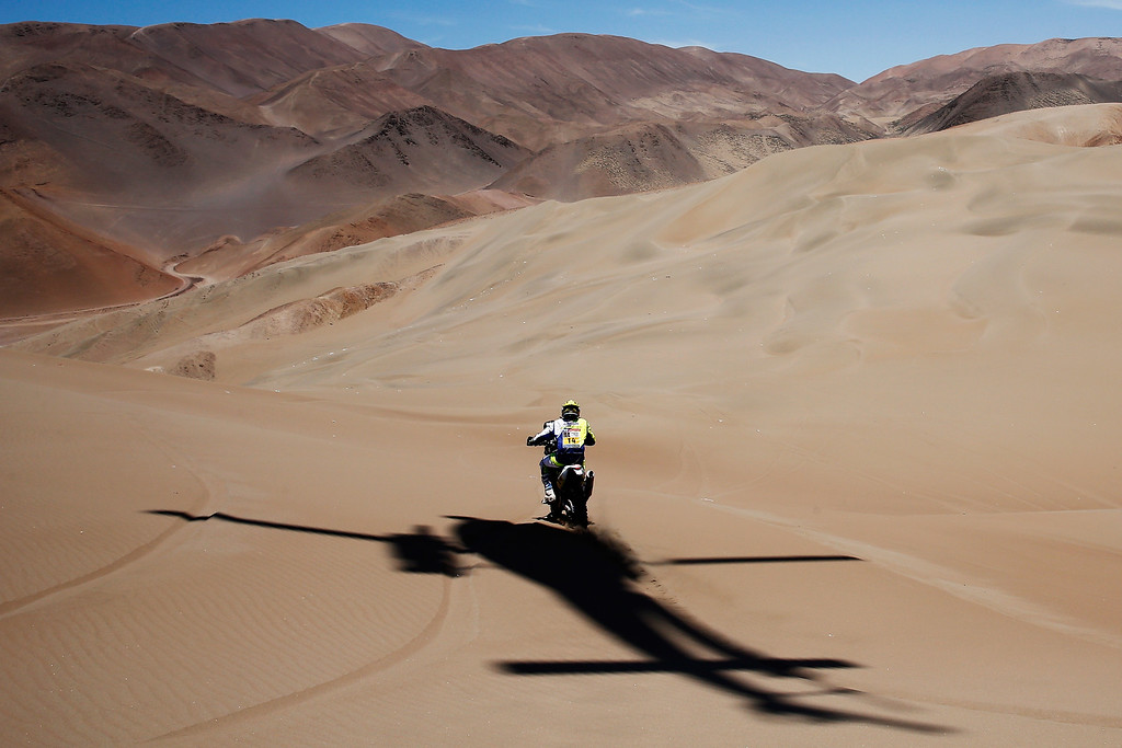 . IQUIQUE, CHILE - JANUARY 09:  #14 Alain Duclos of France riding for Sherco TVS Rally Factory RTR450 competes with the shadow of the TV helicopter following him during day 6 of the Dakar Rallly between Antofaasta and Iquique on January 9, 2015 near Iquique, Chile.  (Photo by Dean Mouhtaropoulos/Getty Images)