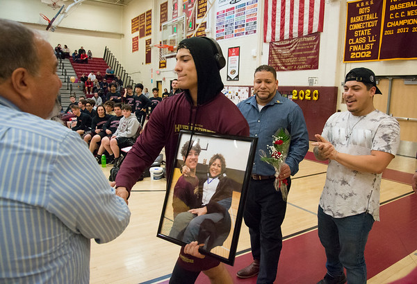 01/29/20 Wesley Bunnell | StaffrrNew Britain wrestling defeated Farmington on Senior Night on Wednesday January 29, 2020. Isaiah Medina holds a photo Ivette Medina who passed away as he shakes hands with Athletic Director Len Corto walking up with his father Frank Medina and brother Dominick Medina.