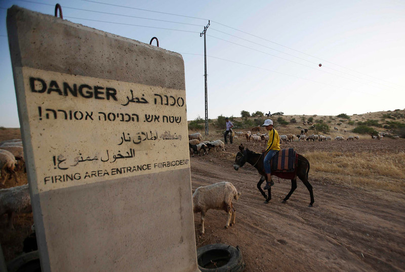 . A Bedouin boy rides a donkey near a sign in the West Bank village of Wadi al-Maleh, near the border with Jordan April 29, 2013. Israeli soldiers on Monday evicted several hundred Bedouins from the village in the occupied West Bank after the army declared the area a live-fire training zone. The residents of Wadi al-Maleh, a village mostly inhabited by shepherds in the arid area, had almost all left their homes by an evening curfew and retreated to neighboring villages, a local leader told Reuters. REUTERS/Mohamad Torokman