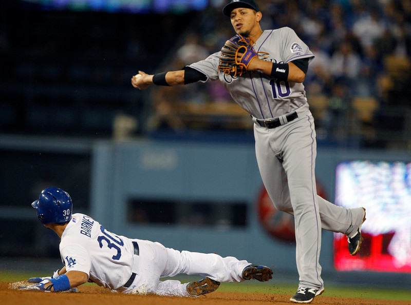 . Colorado Rockies shortstop Cristhian Adames (10) throws to first after forcing out Los Angeles Dodgersí Darwin Barney (30), but not in time to get Alex Guerrero at first in the sixth inning of a baseball game Saturday, Sept. 27, 2014, in Los Angeles. (AP Photo/Alex Gallardo)