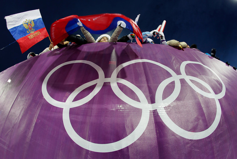 . Fans watch the men\'s biathlon 10k sprint, at the 2014 Winter Olympics, Saturday, Feb. 8, 2014, in Krasnaya Polyana, Russia. (AP Photo/Charlie Riedel)