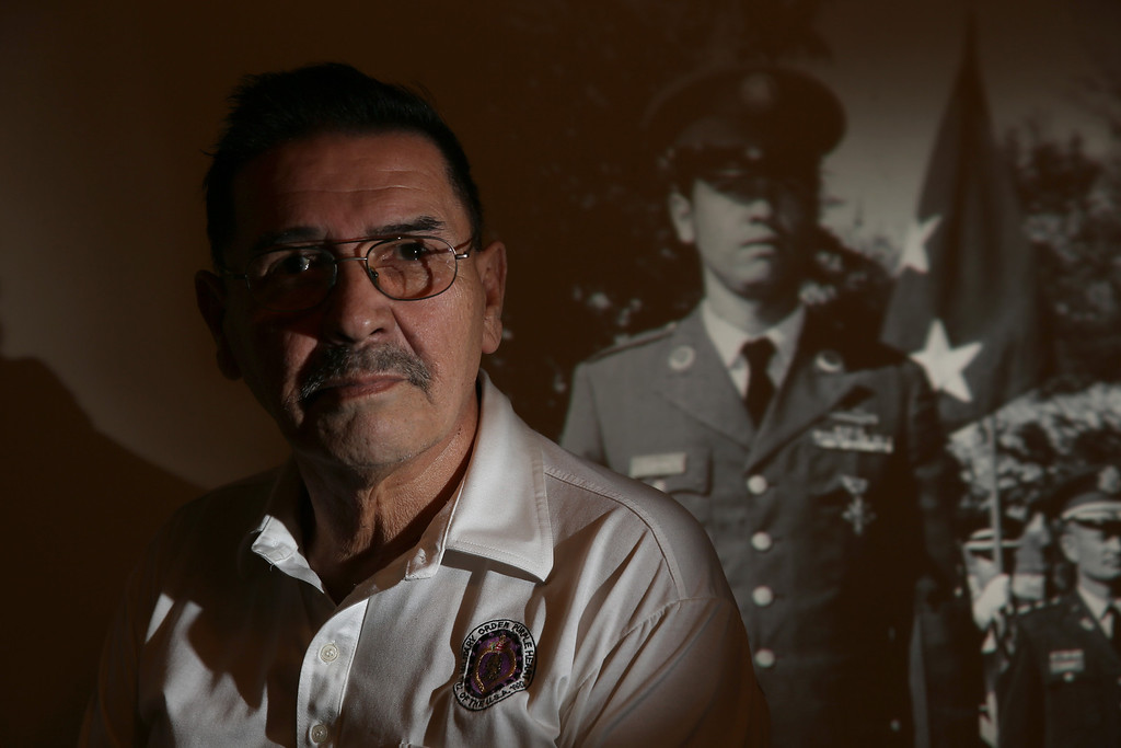 . U.S. Army Specialist Four Santiago J. Erevia, a Vietnam War veteran is seen with an image of himself in his uniform projected on the wall behind him at his home on March 11, 2014 in San Antonio, Texas.  (Photo by Joe Raedle/Getty Images)