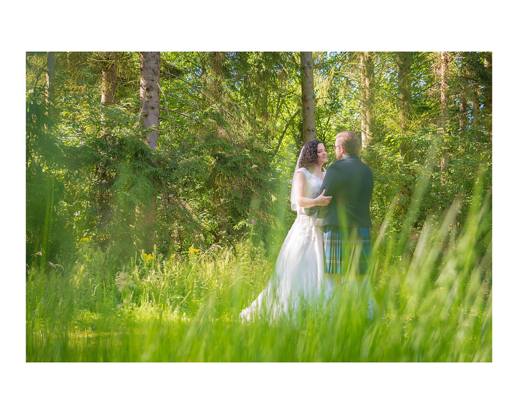 Wedding Photography of Sara & Andrew, Fernie Castle, Cooper, Fife, Photograph is of the Bride & Groom standing in the grass of the woods