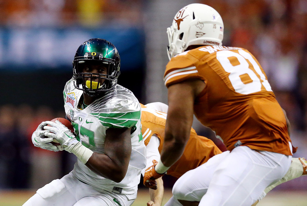 . Linebacker Derrick Malone #22 of the Oregon Ducks runs after an interception as tight end Greg Daniels #81 of the Texas Longhorns defends during the Valero Alamo Bowl at the Alamodome on December 30, 2013 in San Antonio, Texas.  (Photo by Ronald Martinez/Getty Images)