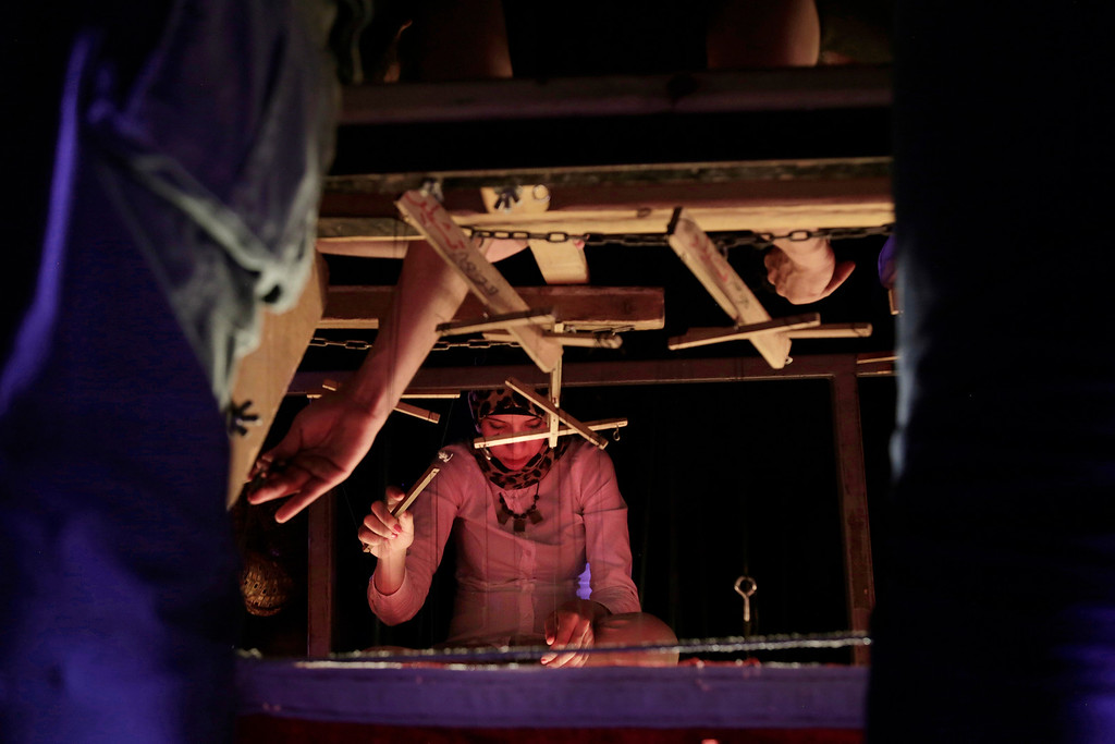 . In this May 3, 2018 photo, a puppeteers of Egyptian artist Mohamed Fawzi Bakkar\'s team moves a puppet during a preformance at the El Sawy Cultural Center, in Cairo, Egypt. Bakkar designs and builds marionettes from scratch, hoping to revive a traditional art. The 32-year-old spends hours or even days designing puppets inspired by Egyptian life -- farmers, street vendors, butchers and the occasional celebrity. (AP Photo/Nariman El-Mofty)