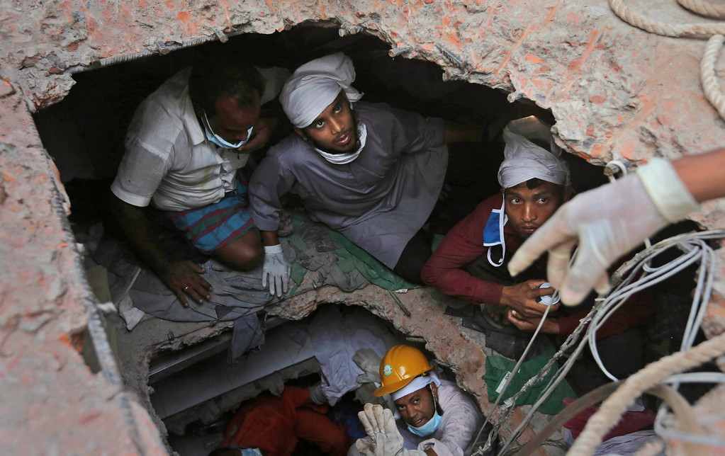 . In this April 28, 2013 file photo, Bangladeshi rescue workers search for survivors as they are seen through a hole in the roof a building that collapsed Wednesday in Savar, near Dhaka, Bangladesh.  (AP Photo/Kevin Frayer File)