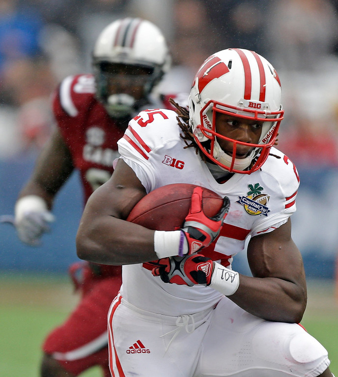 . Wisconsin running back Melvin Gordon, front, runs for yardage past the South Carolina defense during the first half of the Capital One Bowl NCAA college football game in Orlando, Fla., Wednesday, Jan. 1, 2014.(AP Photo/John Raoux)
