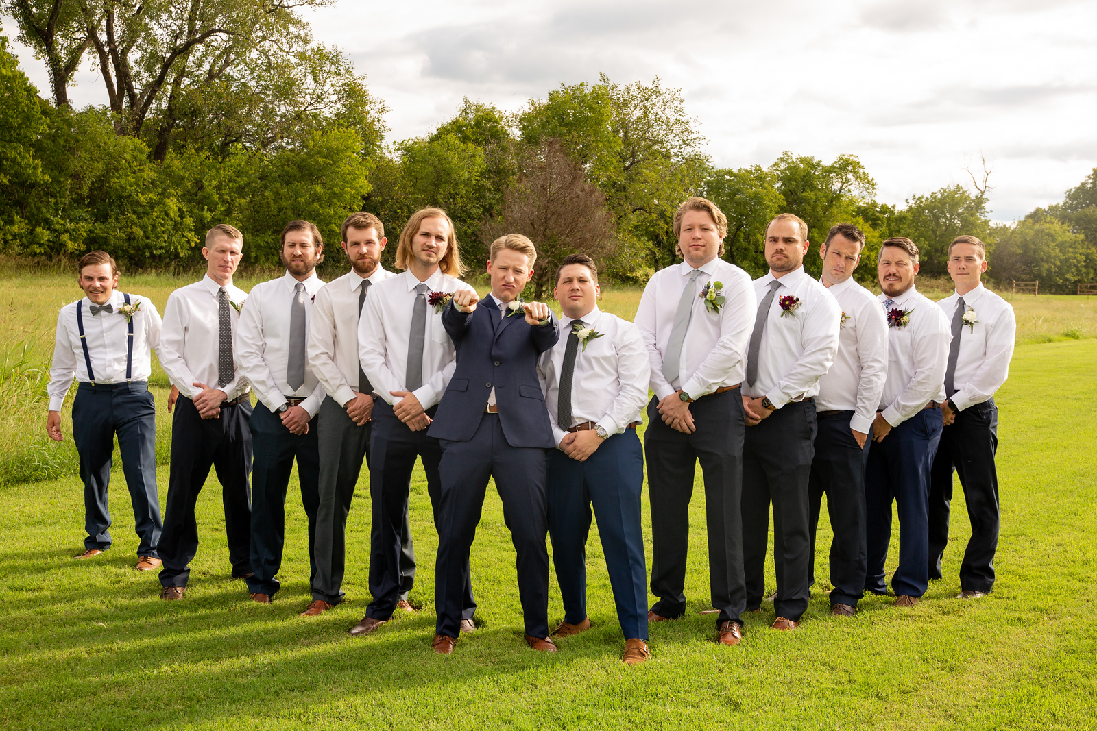 groom pointing to the camera with his ten groomsmen standing next to and behind him with serious looks on their faces