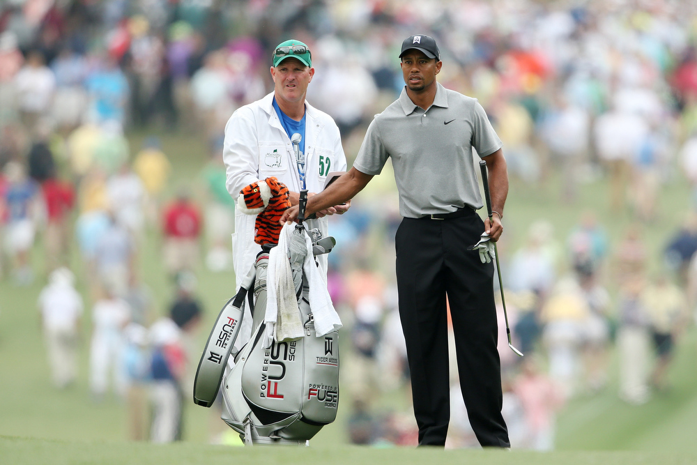 Description of . Tiger Woods of the United States stands with caddie Joe LaCava on the first hole during the first round of the 2013 Masters Tournament at Augusta National Golf Club on April 11, 2013 in Augusta, Georgia.  (Photo by Andrew Redington/Getty Images)