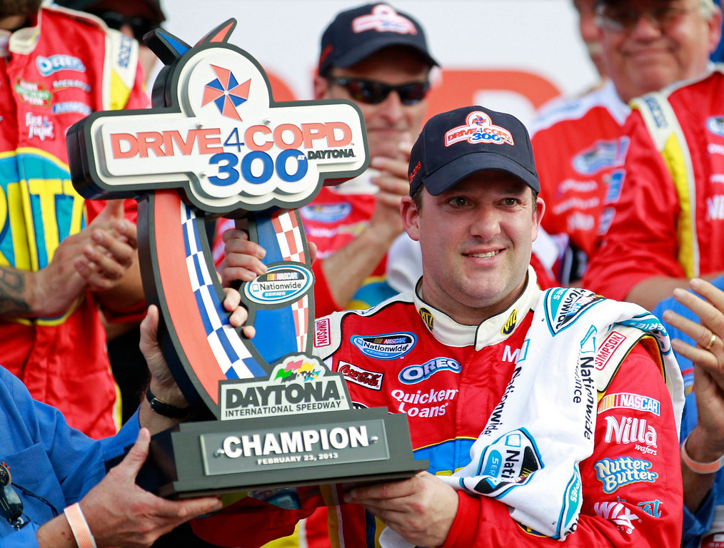 . NASCAR driver Tony Stewart holds the trophy after winning the NASCAR Nationwide Series DRIVE4COPD 300 race at the Daytona International Speedway in Daytona Beach, Florida February 23, 2013. The Daytona 500 NASCAR Sprint Cup race is scheduled for February 24.  REUTERS/Joe Skipper