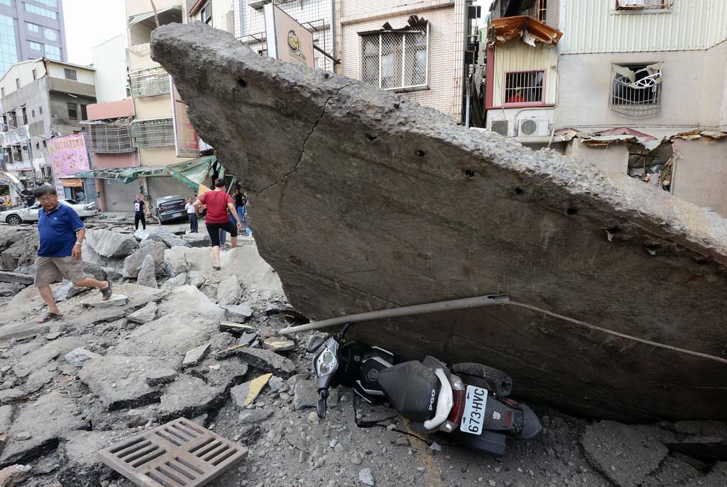 . A local resident (L) walks past a slab of concrete resting on a motorbike after a gas explosion ripped through a neighborhood in the southern Taiwan city of Kaohsiung on August 1, 2014. A series of powerful gas blasts killed at least 25 people and injured up to 267 in the southern Taiwanese city of Kaohsiung, overturning cars and ripping up roads as terrified residents fled an inferno.     AFP PHOTO  / SAM YEH/AFP/Getty Images
