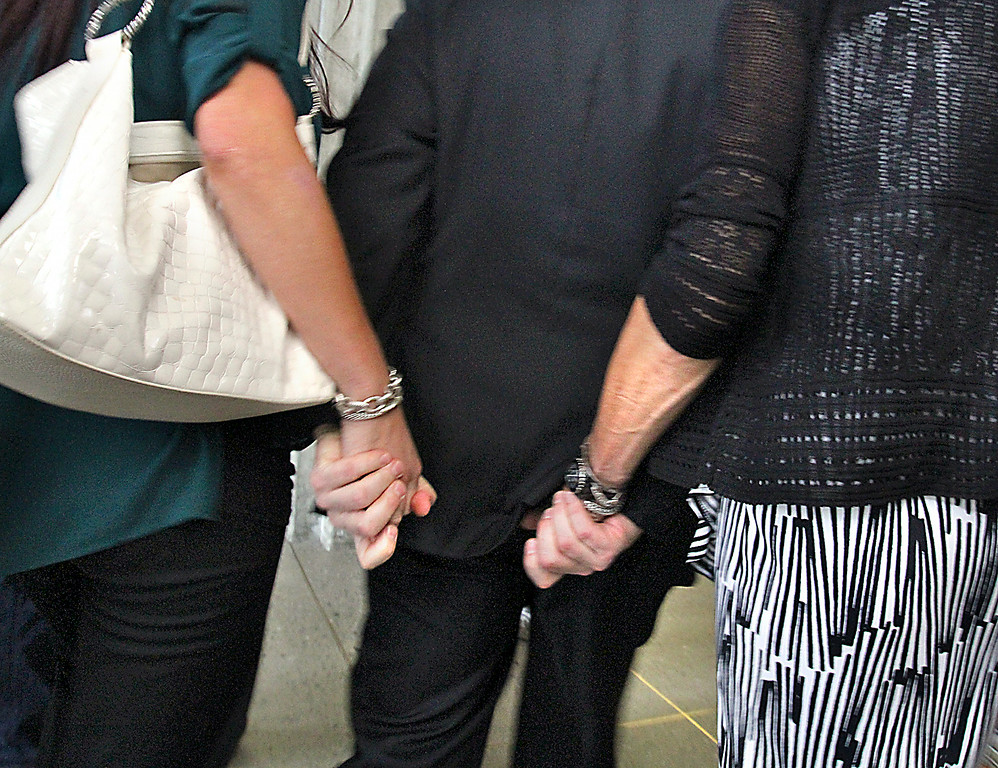 . Bart Tichelman holds tightly to the hands of his daughter Monica and wife Leslie as he leaves the arraignment on mansalughter chargers of his daughter Alix Tichelman on Wednesday. (Shmuel Thaler -- Santa Cruz Sentinel)