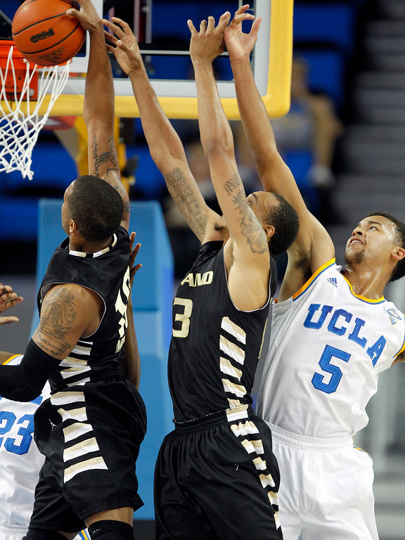 . Oakland guard Duke Mondy, left and forward Tommie McCune, center, compete for a rebound with UCLA guard Kyle Anderson (5) in the first half of an NCAA college basketball game Tuesday, Nov. 12, 2013, in Los Angeles. (AP Photo/Alex Gallardo)