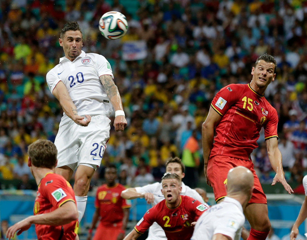 . United States\' Geoff Cameron heads the ball at the Belgium goal past Belgium\'s Daniel Van Buyten during the World Cup round of 16 soccer match between Belgium and the USA at the Arena Fonte Nova in Salvador, Brazil, Tuesday, July 1, 2014. (AP Photo/Marcio Jose Sanchez)